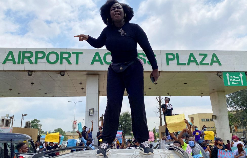 A demonstrator stands atop a vehicle and shouts slogans as others carry banners while blocking a road leading to the airport, during a protest over alleged police brutality, in Lagos, Nigeria October 12, 2020.