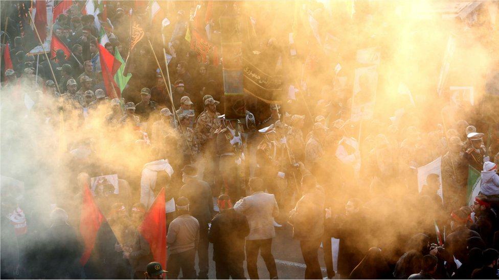 An Iranian military parade is seen behind a smoke screen from burning incense as crowds gather to pay homage to military commander Qasem Soleimani, Iraqi paramilitary chief Abu Mahdi al-Muhandis and other victims of a US drone attack, in the capital Tehran on 6 January, 2020