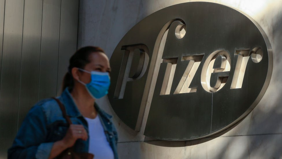 Woman walks past Pfizer sign