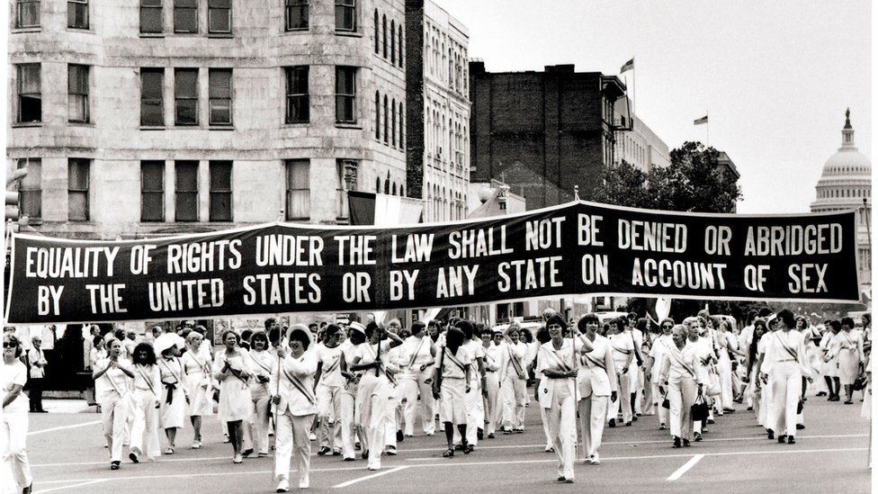 Women carry a large banner down Pennsylvania Avenue demanding equality, 26 August 1977