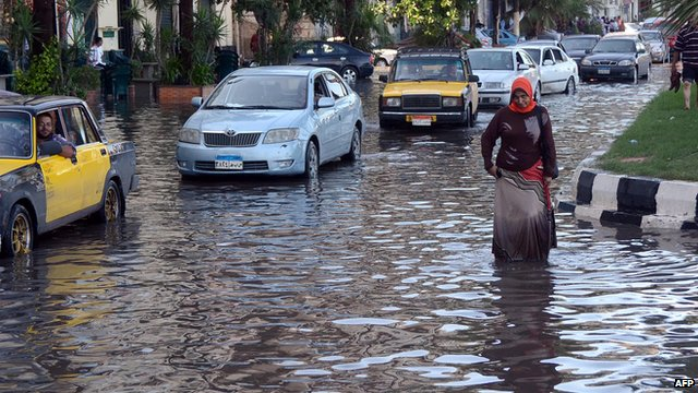 In Egyptian woman walks in a flooded street in Egypt's northern coastal city of Alexandria