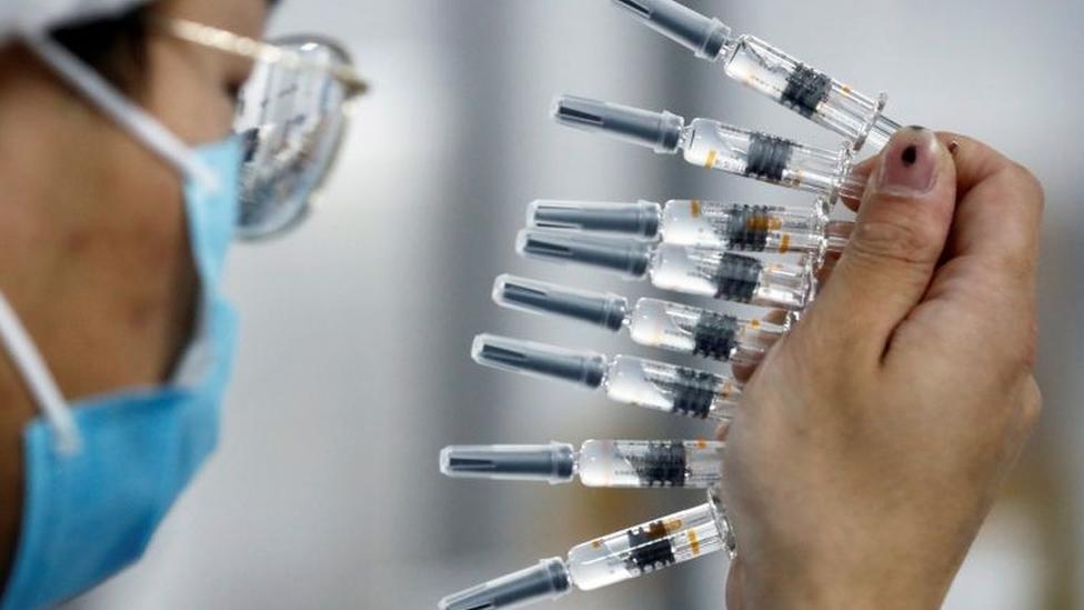 Funcionário de jaleco e máscara, aparecendo de perfil, segura diversas doses de vidro de vacina