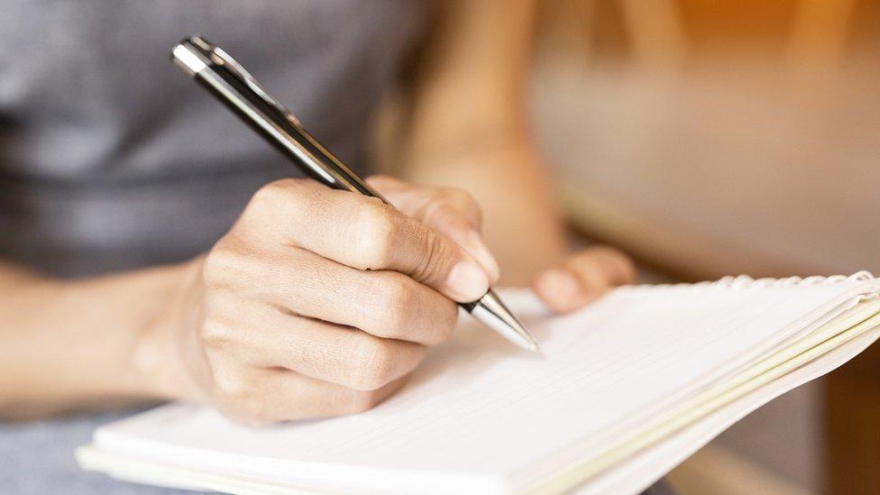 Una mujer escribe en un cuaderno