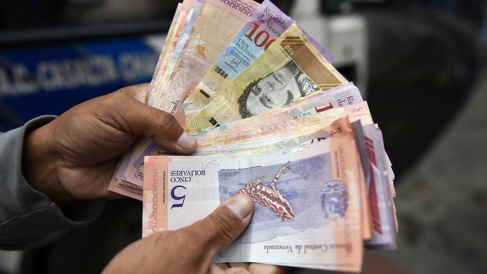 Una mano sosteniendo billetes de bolívares venezolanos