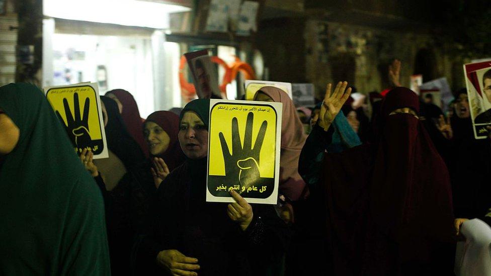 أشخاص يحملون ملصقات للرئيس المصري السابق محمد مرسي وشعار رابعة العدوية أثناء الاحتجاج على النظام في الذكرى الخامسة للثورة المصرية في 2011، في الجيزة