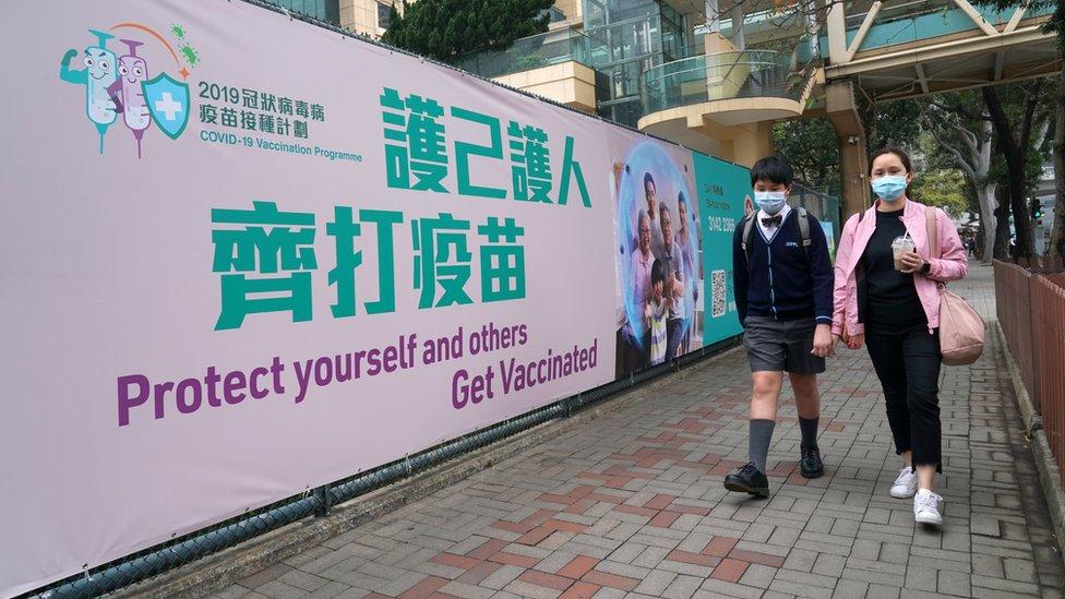 路人走過銅鑼灣香港中央圖書館社區疫苗接種中心外的大型宣傳橫幅(中新社圖片5/3/2021)
