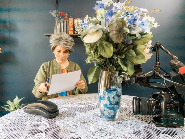 """Jenny Lorenzo repasando el guion de uno de sus segmentos como """"la abuela cubana""""."""