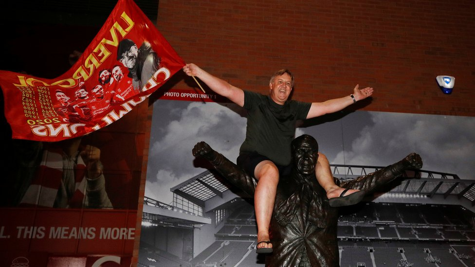 A Liverpool fan celebrates winning the Premier League as he sits on a statue of Bill Shankly outside Anfield