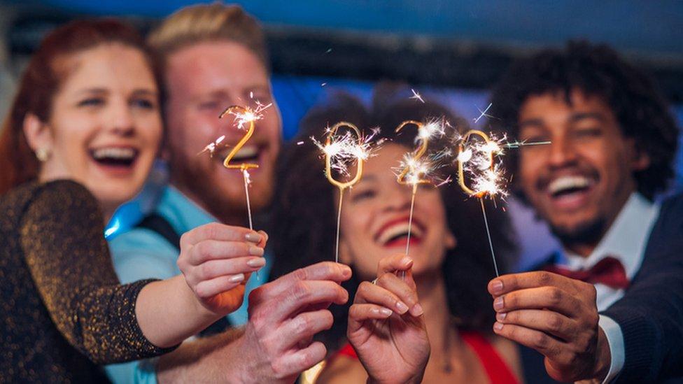 Grupo de amigos celebra 2020 con luces.