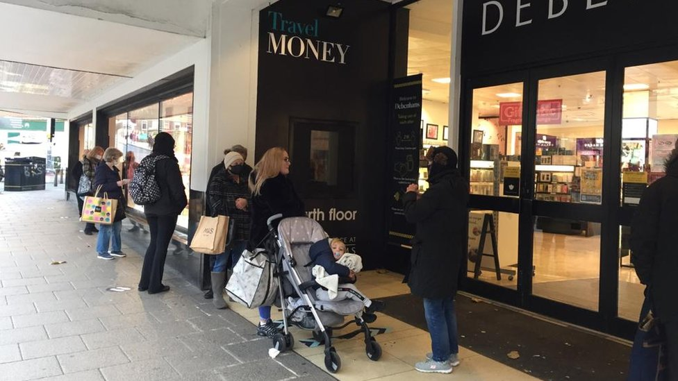 shoppers waiting to enter the Debenhams store in Norwich