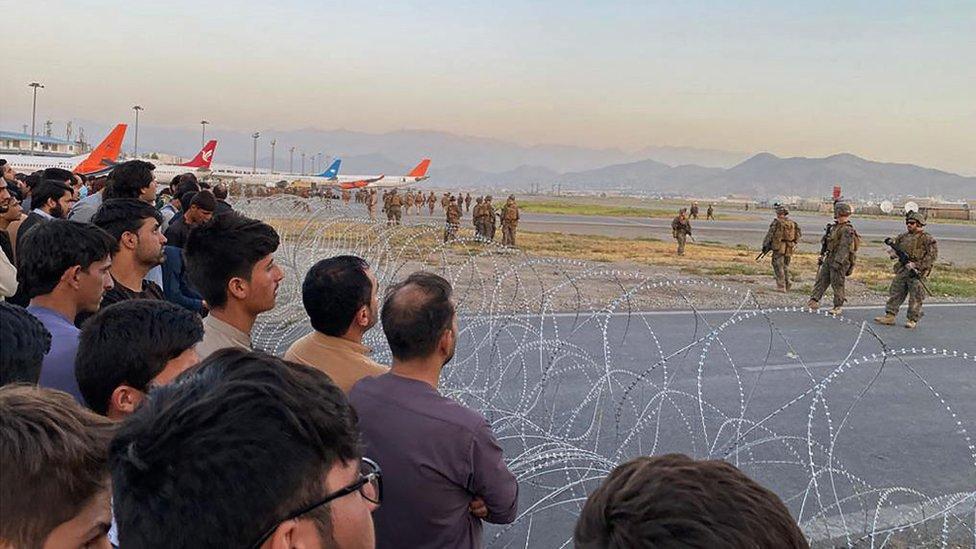 Soldados estadounidenses vigilan el aeropuerto de Kabul, mientras que civiles están separados por alambres de púas