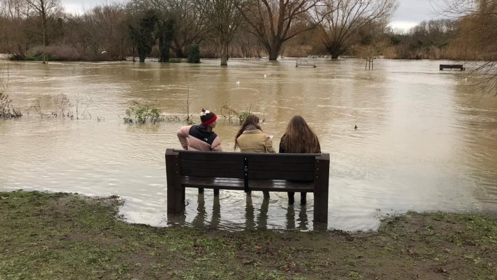 Three women sat on bench in floodwaters in Bedford