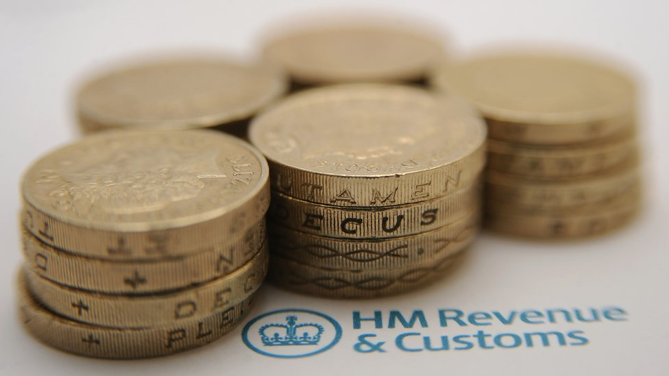 One pound coins stacked on top of HM Revenue and Customs letter headed document