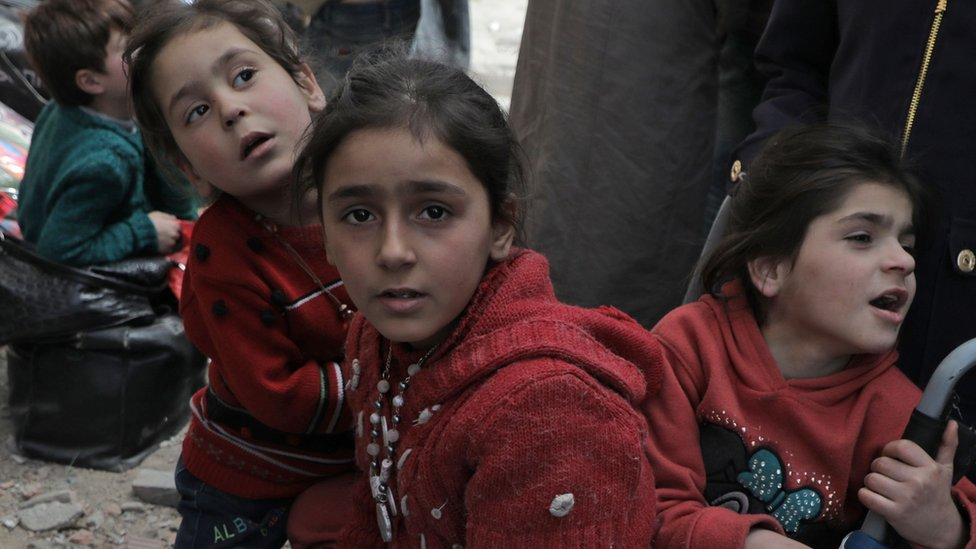 Children wait to be evacuated from the town of Douma, in the rebel-held Eastern Ghouta region (22 March 2018)