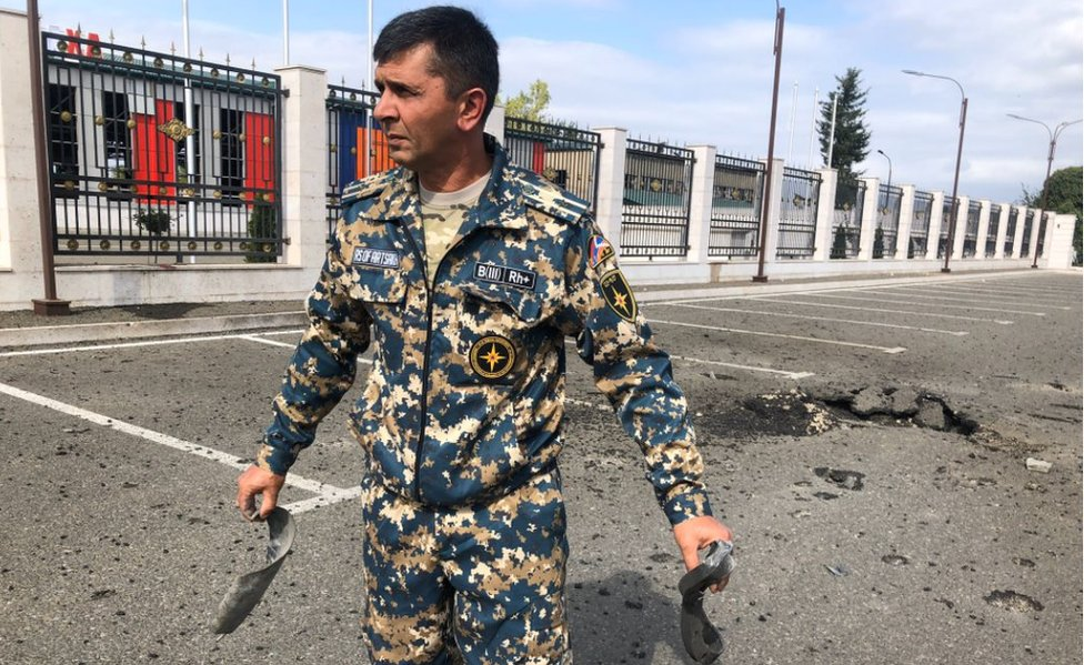 An officer in Stepanakert shows parts of a rocket that came down near the emergency service department
