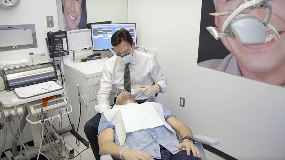 Dr.Bill atendiendo en su consultorio