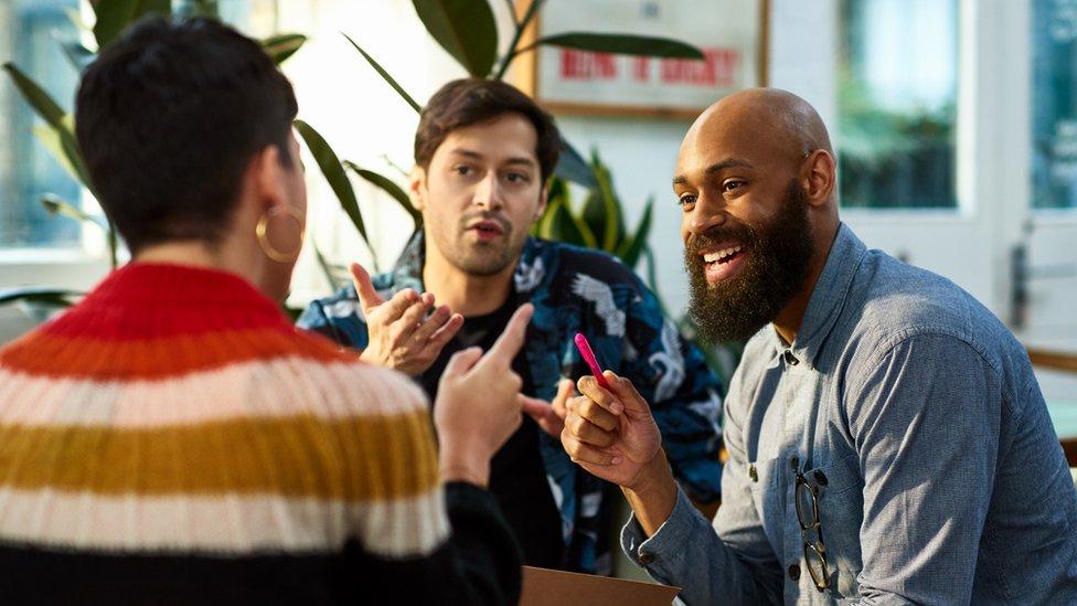 Tres personas conversan animadamente.
