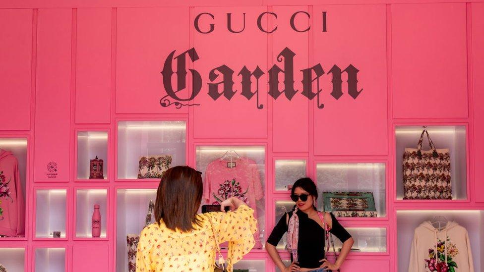 Dos mujeres recorren la colección de Gucci Aria en la exposición por el centenario de Shanghái.