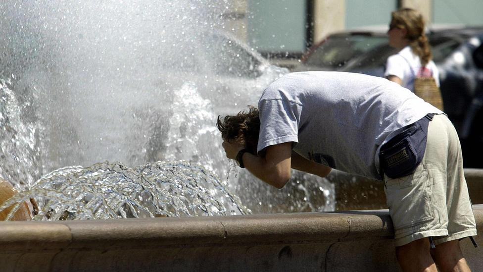 Hombre refrescándose en una fuentes