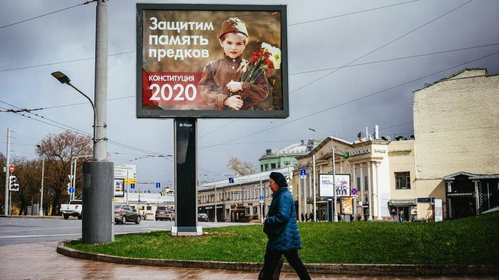 امرأة تمرّ على لوحة إعلانات عليها صورة طفلة ترتدي الزي الرسمي للجيش