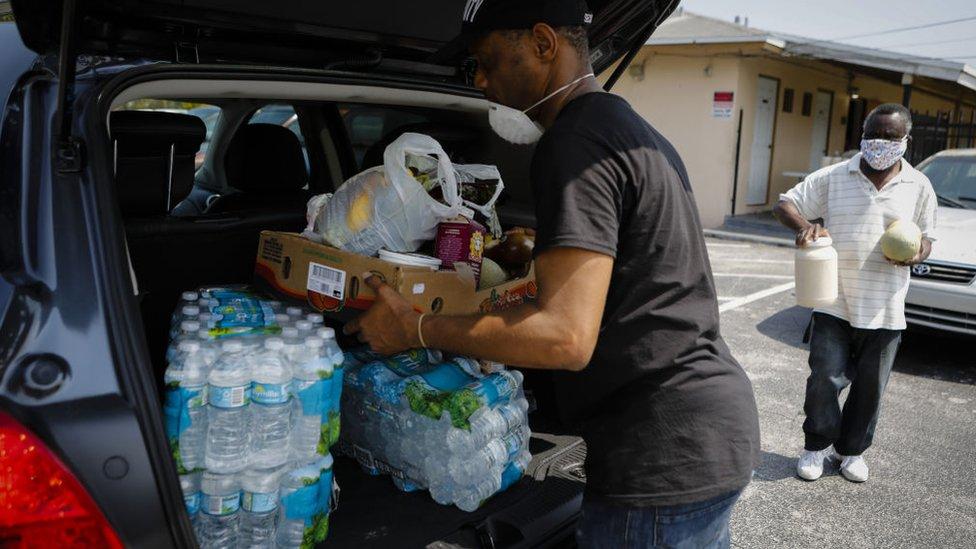 Un hombre llena su maletero de agua y alimentos