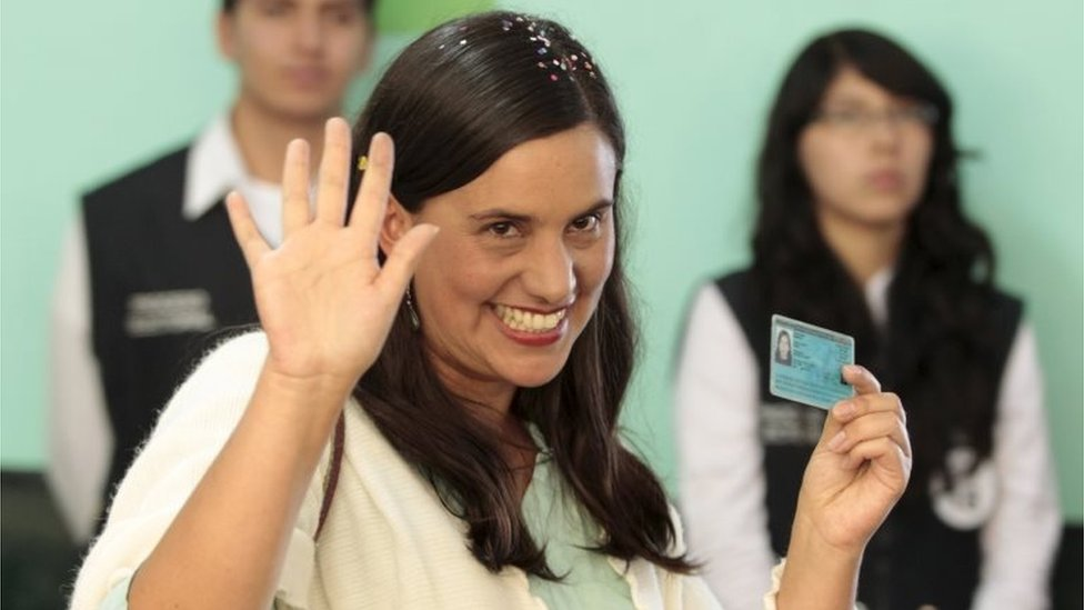 """Peru's presidential candidate Veronika Mendoza of """"Frente Amplio"""" party, shows her I.D. to the media after casting her ballot during election in the district of San Sebastian in Cuzco, April 10, 2016."""