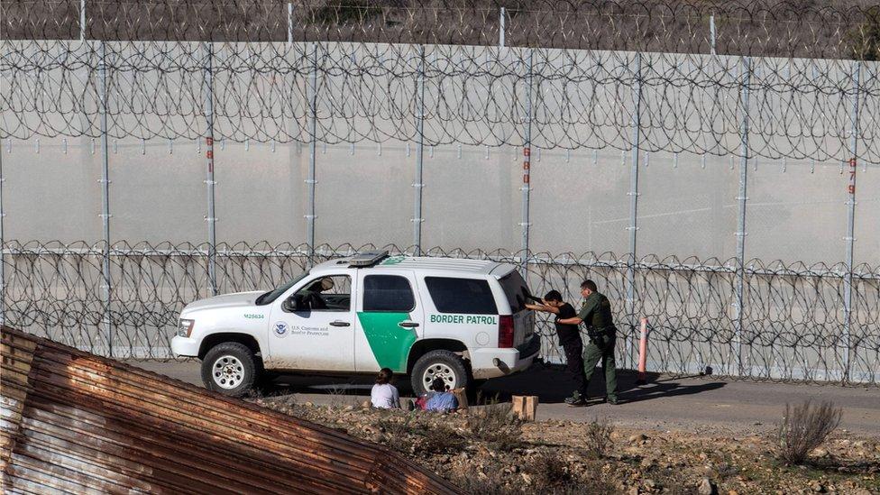 Un hombre es revisado por patrulleros en la frontera