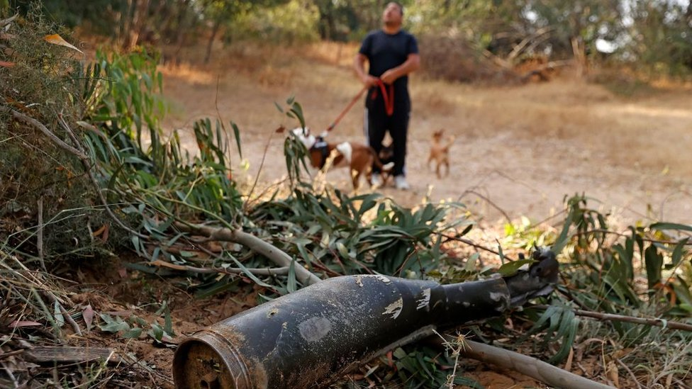 A man walks his dogs next to a destroyed missile