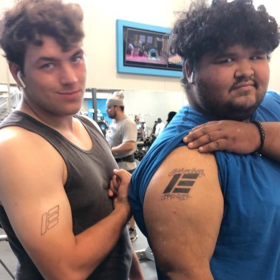 Two men show off tattoos on their upper arms. Both tattoos are of the Etika logo which looks like a large capital e.
