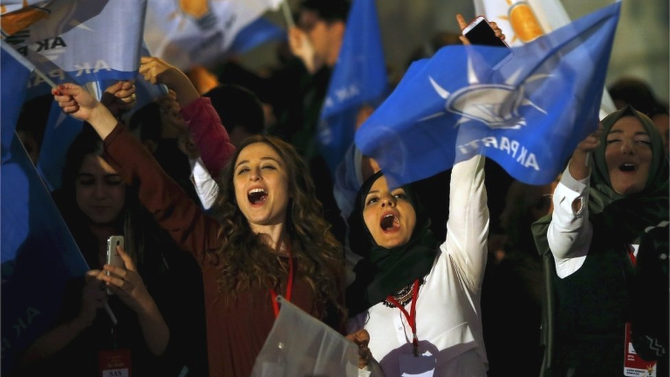 Women wave flags outside the AK Party headquarters in Ankara