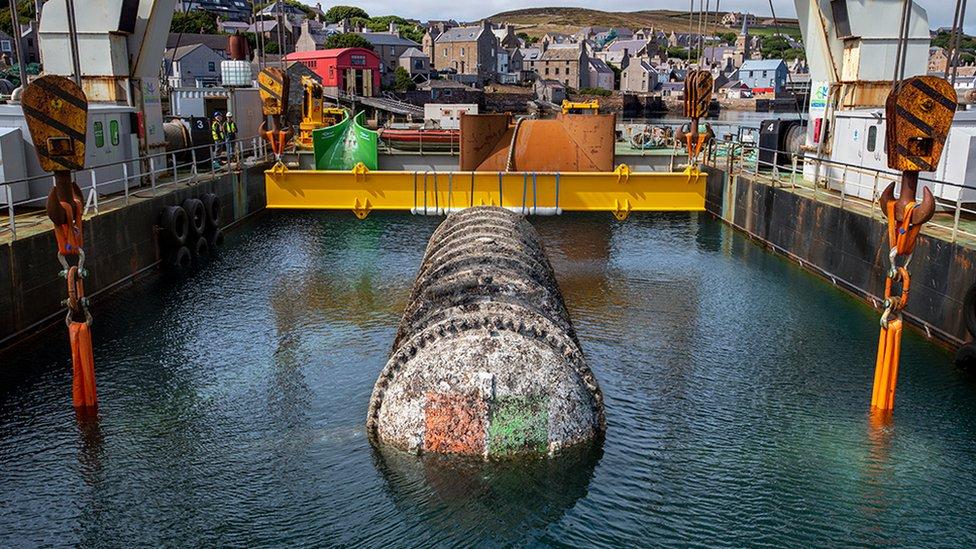 Una grúa levanta del mar un cilindro largo y blanco cubierto de mugre. El logotipo de Microsoft solo es visible en la tapa del extremo debajo de una capa de suciedad