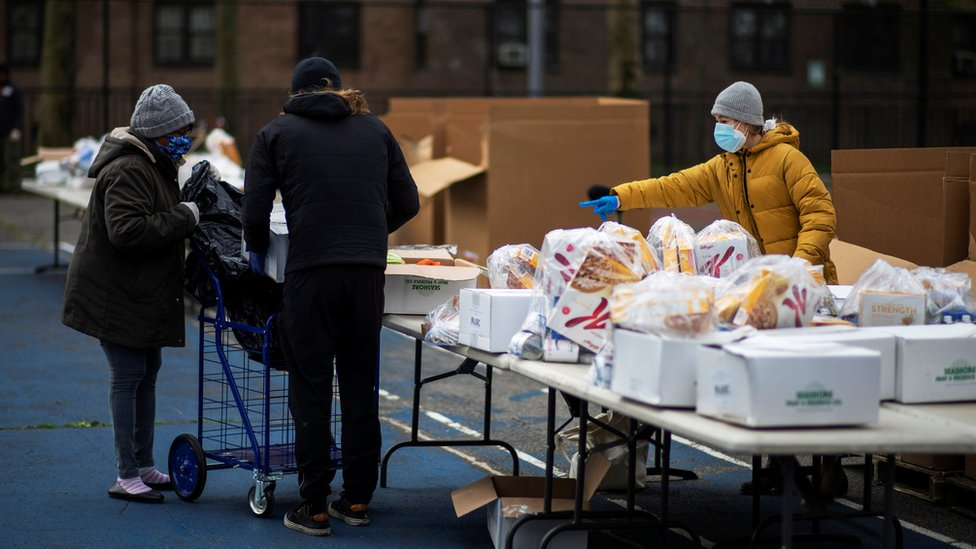 A woman organizes food donated by City Harvest Mobile Market Food Distribution Center, during the outbreak of the coronavirus disease (COVID-19) in the Brooklyn borough of New York, U.S., April 15, 2020.