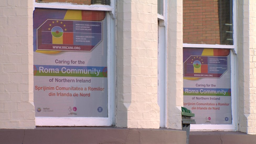 Signs in thee windows of the Romanian Roma Community Association of Northern Ireland offices