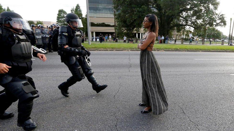 Una joven se mantiene de pie mientras funcionarios antimotines se le acercan