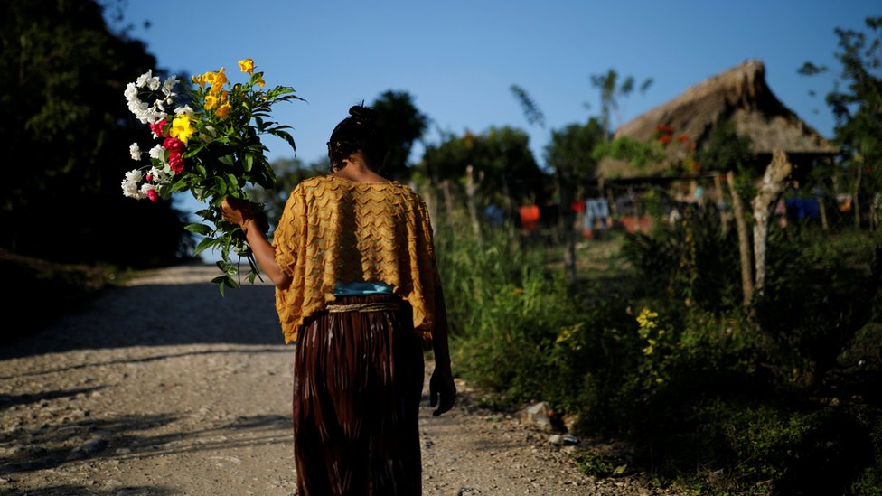A woman walks with flowers near the home of Jakelin Caal in San Antonio Secortez village, Guatemala