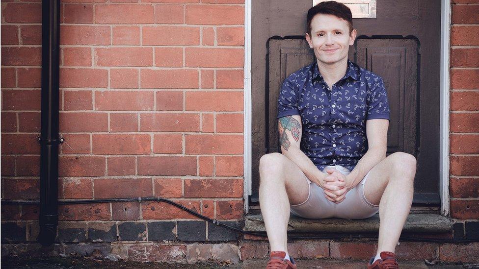Alex Feis-Bryce sentado na frente de uma casa com as mãos cruzadas