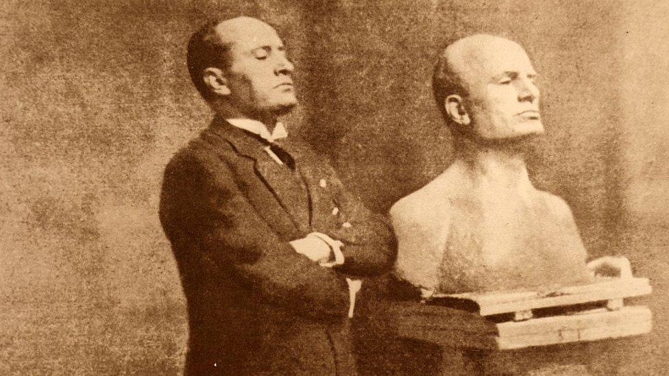 Mussolini posa junto a un busto.