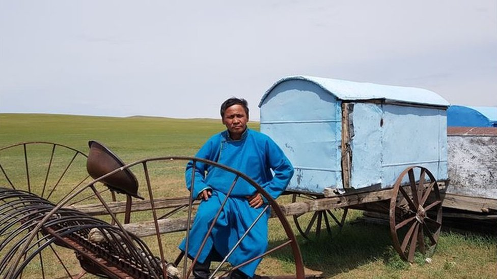 Batmunkh sitting on farming equipment