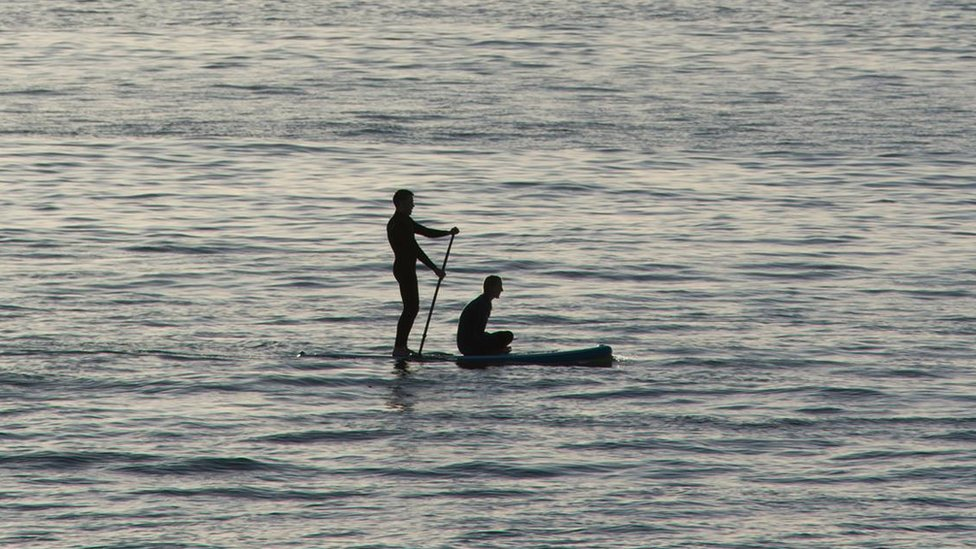 Two paddleboarders taking in the sights near South Beach in Aberystwyth