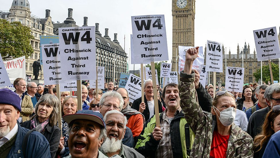 Protesters hold signs during a rally against a third runway at Heathrow airport, in Parliament Square on 10 Oct 2015