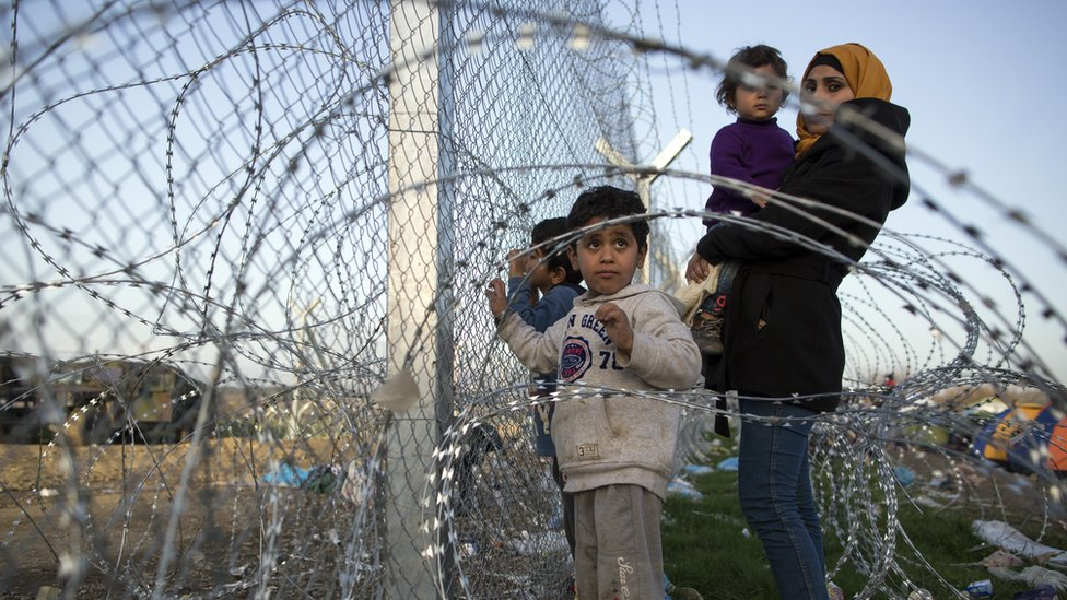 أسرة سورية قرب السلك الشائك الحدودي