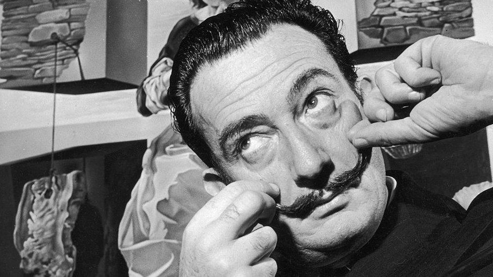 Salvador Dalí tocándose el bigote.