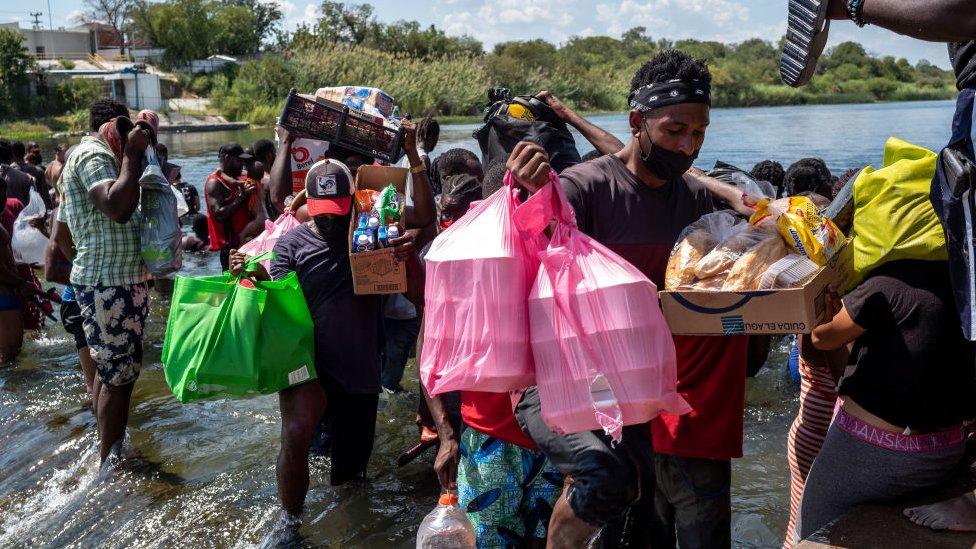 Migrantes con suministros cruzando el río.