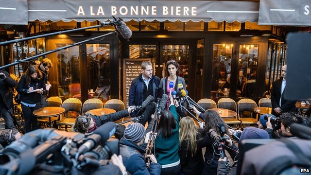 """Cafe managers Audrey Bily (R) and Romain Debray (L), speak to media outside the cafe during the reopening of the """"A la Bonne biere"""" two weeks after the Paris terror attacks, in Paris, France, early 04 December 2015."""