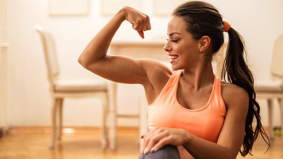Una mujer con ropa deportiva haciendo fuerza con el bíceps.