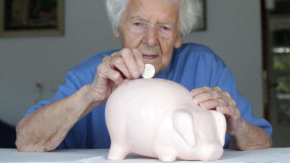 Mujer adulta deposita una moneda en una alcancía con forma de cerdo rosa.