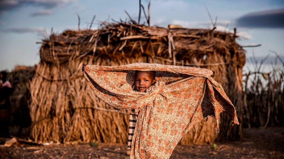 ولد يقف أمام منزله في منطقة توركانا شمال غربي كينيا التي تعرضت للجفاف.