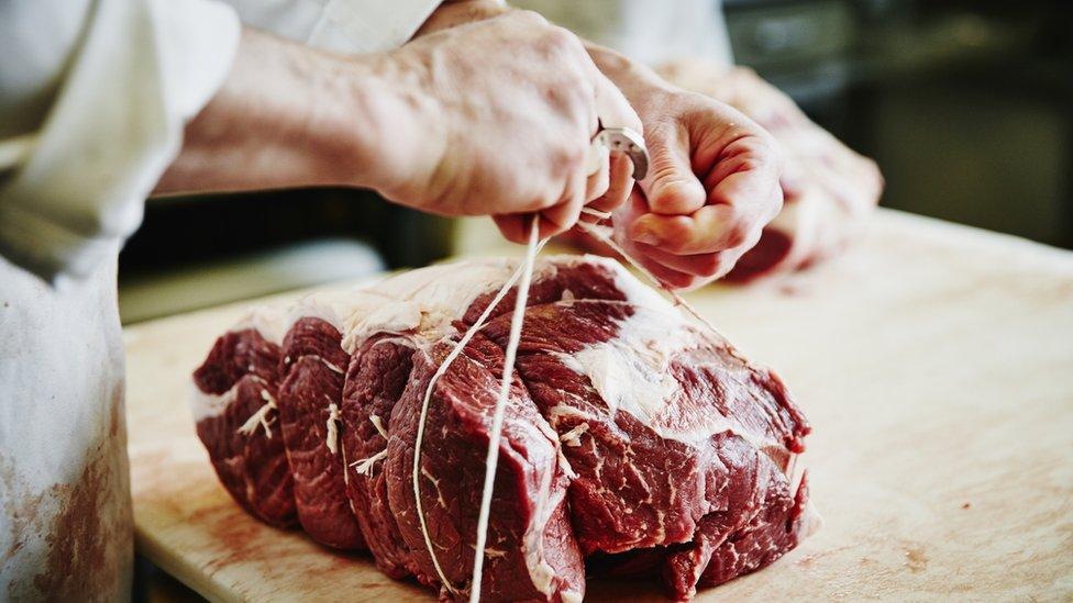 肉店屠夫在捆綁一塊牛肉