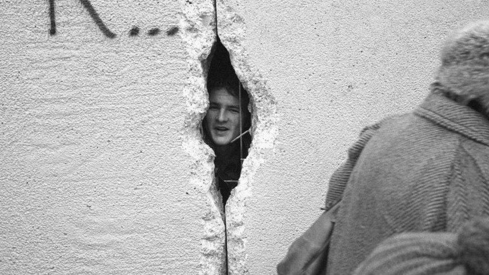 رجل ينظر من خلال ثقب في سور برلين