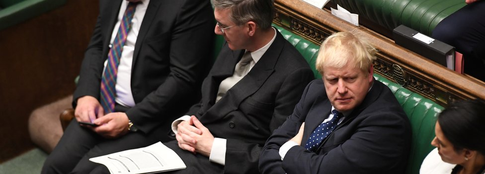 Boris Johnson sitting in the House of Commons
